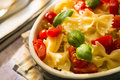 Closeup of Italian Farfalle pasta with tomatoes and basil Royalty Free Stock Photo