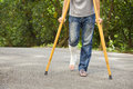 Closeup of leg on bandage with crutches walking road Royalty Free Stock Photos