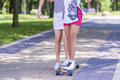 Closeup of Legs of Caucasian and African American Teenager Girl Skating Longboard Outdoors Royalty Free Stock Photo