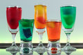 Closeup of a line of colorful cocktails resting on the bar with led lighting at a club Royalty Free Stock Images