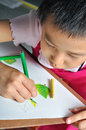 Closeup little asian girl hand draw her  picture with color penc Royalty Free Stock Photo