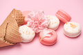 Closeup of macarons group with waffle cones and Carnation flower on pink surface Royalty Free Stock Photo