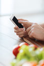 Closeup of male hand pointing finger to smartphone cooking technology and home concept Stock Photography