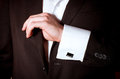 Closeup of a man in black suit correcting sleeve Stock Image