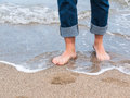 Closeup of man feets walk in the waves on sand beach Royalty Free Stock Photo