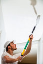 Closeup of man painting the ceiling holding roller pin and Stock Photography