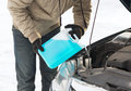 Closeup of man pouring antifreeze into water tank Royalty Free Stock Photo