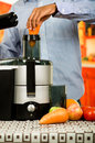 Closeup man's hands using juice maker, inserting carrot into machine, healthy lifestyle concept Royalty Free Stock Photo