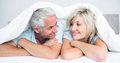 Closeup of a mature couple lying in bed portrait at home Stock Photos