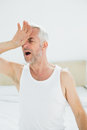 Closeup of a mature man yawning in bed at home Royalty Free Stock Photography