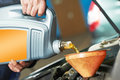 Closeup mechanic hand pouring oil into car motor Royalty Free Stock Images