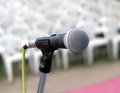Closeup of microphone against chairs seating background Royalty Free Stock Images