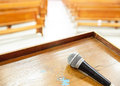 Closeup microphone in empty church with empty pews Royalty Free Stock Photography
