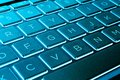 Closeup of a modern silver laptop computer keyboard. Laptop keyboard. Detail of the new and ergonomic computer keyboard. Blue tone Royalty Free Stock Photo