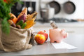 Closeup on money in piggy bank and purchases from local market table Stock Photography