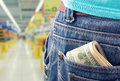 Closeup of money in the pocket against grocery market Stock Photo