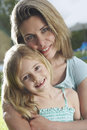 Closeup of mother hugging daughter outdoors portrait a happy Royalty Free Stock Images