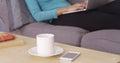 Closeup of mug and smartphone on coffee table Stock Photo