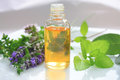 Closeup oil bottle fresh green herbs aromatic flowers alternative medicine concept Stock Photography