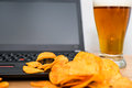 Closeup of open laptop with chips scattered on keyboard and glas glass beer in background stock photo Royalty Free Stock Photos