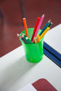 Closeup of organizer with colorful pencils on desk in classroom Royalty Free Stock Photo