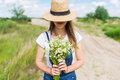 Closeup outdoor portrait of a beautiful young woman in hat. Attractive happy girl in a field with bouquet of flowers Royalty Free Stock Photo
