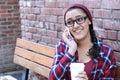 Closeup outdoor portrait of cute happy brunette ethnic teenage girl with takeaway coffee talking on smartphone Stock Photo