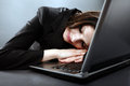 Closeup of overworked businesswoman tired sleeping on her laptop keyboard in pose on grey background Royalty Free Stock Photos