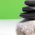 Closeup partial view stacked smooth black basalt spa stones balancing one another conceptual alternative therapy peace pampering Stock Image