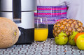 Closeup partly visible juice maker sitting on table next to pineapple, pear and apple, hand holding onto glass of yellow Royalty Free Stock Photo