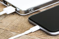 Closeup phone charging white power bank portable