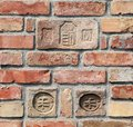 Closeup photo about a brick wall built by light brown bricks with coat of arms Stock Photos
