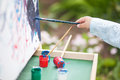 Closeup photo, child painting on easel