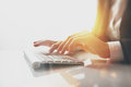 Closeup photo of female hands typing text on a wireless keyboard. Business woman working at the office. Visual effects Royalty Free Stock Photo