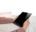 Closeup photo of man holding tablet on table with blueprints Royalty Free Stock Photo