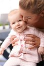 Closeup photo of mother kissing happy baby holding and tender little daughter Royalty Free Stock Photo