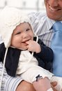 Closeup photo of pretty baby girl in father s arms smiling Royalty Free Stock Images