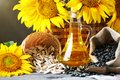 Closeup photo of sunflowers and sunflower oil with seeds on on a wooden table. Bio and organic concept of the product. Royalty Free Stock Photo
