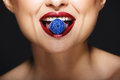 Closeup picture of cheerful girl`s lips holding sweeties with teeth. Royalty Free Stock Photo
