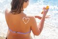Closeup picture of sunscreen spf filtred tan lotion heart shape drawing on woman back over blue sea background Stock Photos