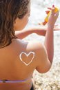 Closeup picture of sunscreen spf filtred tan lotion on woman back over blue sea background Royalty Free Stock Images