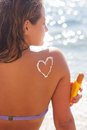 Closeup picture of sunscreen tan lotion on woman heart shape drawing back over blue sea background Royalty Free Stock Photos