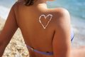 Closeup picture of sunscreen tan lotion on woman heart shape drawing back over blue sea background Stock Images
