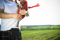 Closeup picture of young man playing pipes in image close up enjoying scotish traditional kilt on green outdoors copy space summer Stock Images