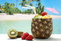 Closeup pineapple cocktail with fruit kiwi and strawberry on the tropical beach Stock Images