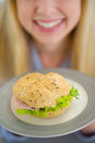 Closeup on plate with sandwich in hand of girl Royalty Free Stock Photo
