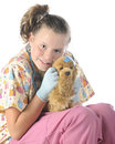 Closeup playing vet closel up of a pretty elementary veterinarian hugging her injured toy pup on a white background Stock Photography