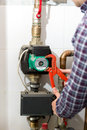 Closeup of plumber repairing heating system with red pliers Royalty Free Stock Photo