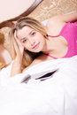 Closeup portrait of beautiful attractive charming sweet young blond woman in crimson shirt with tablet pc computer lying in bed Stock Photography