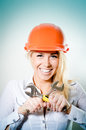 Closeup portrait of beautiful charming young woman happy smiling in a helmet with two wrench looking at camera on blue background Royalty Free Stock Image